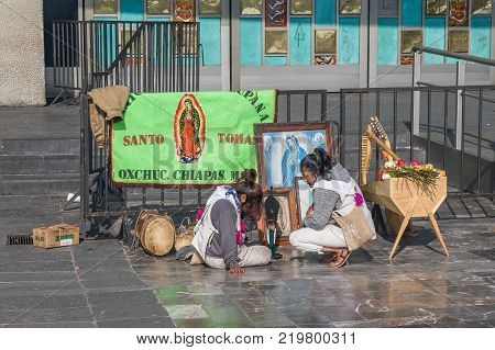 VILLA OF GUADALUPE MEXICO CITY DECEMBER 04 2017 - Two pilgrim girls from the region of Santo Tomas Oxchuc in Chiapas Mexico perform a religious ritual to an image of the Virgin of Guadalupe.