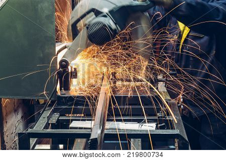 Electric circular grinder in metalwork factory. Worker cuts metal, close up. Sparks while grinding steel or iron parts, toned