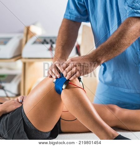 Electrical stimulation in physical therapy. Therapist positioning electrodes on a patient's knee. Woman patient