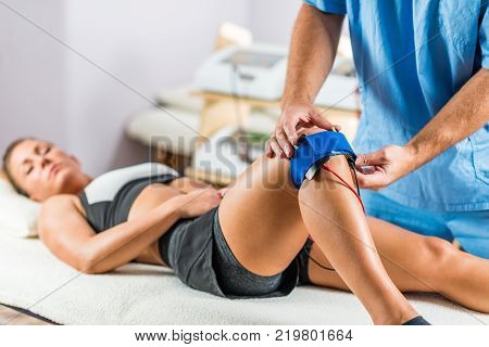 Electrical stimulation in physical therapy. Therapist positioning electrodes onto a patient's knee. Woman patient