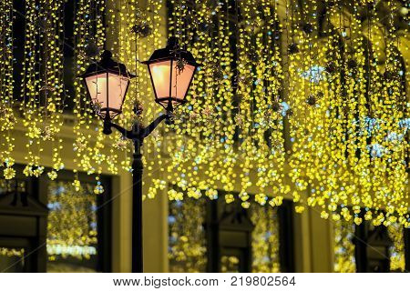 Metal lantern on background of shiny neon garland, as yellowed leaves, vintage tones. Fall and fest backdrop. Festive occasions concept, holiday, Christmas, New Year backdrop