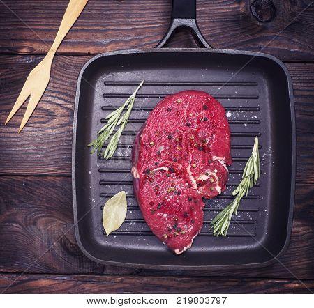 raw beef steak on a black quart pan top view