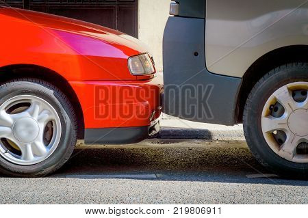 Cars are parked on the street very tightly to each other. A common way of parking in large European cities
