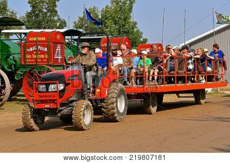 ROLLAG, MINNESOTA, Sept 3. 2017: A Mahindra tractor pulls a loaded people hauler of visitors at the annual WCSTR farm show in Rollag held each Labor Day weekend where 1000's attend.