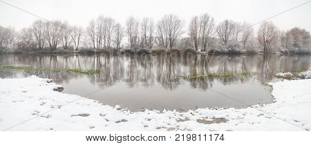 panoramic photo of winter river in the misty morning