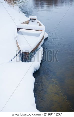 wooden boat on the Bank of winter river