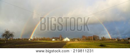 rainbow over the village houses and fields