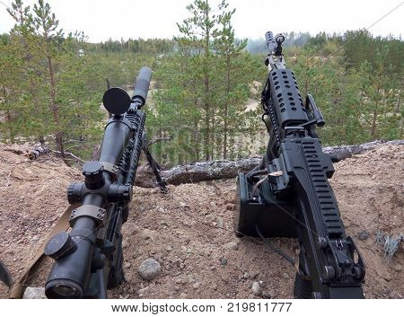 Assault rifle and machine gun on the background of pine forests and sand.