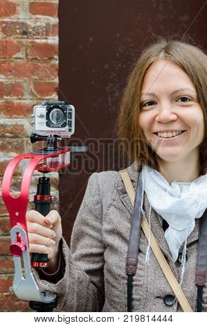 The girl smiles and holds in the hand an action camera on the gimbal stabilizer on the street of Etretat, France, September, 30, 2014.
