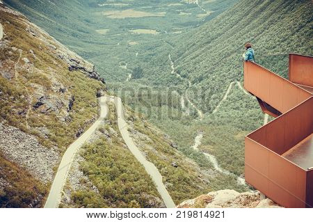 Travel concept. Tourist woman looking at Trolls Path Trollstigen or Trollstigveien winding scenic mountain road from viewing point Norway Europe