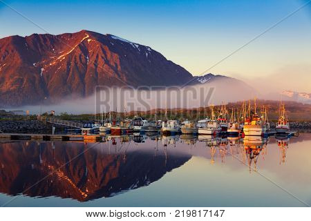 Fishing boats in harbor at midnight sun and fog in Northern Norway, Lofoten Island, Norway - Mountain In Background