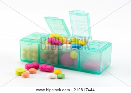 various of colorful pills and tablets of medicine in green pill box on white background.