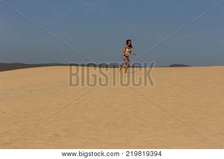 PRAIA DA BORDEIRA, PORTUGAL - AUGUST 20, 2017: Woman at the dunes of the famous beach of Praia da Bordeira. This beach is a part of famous tourist region of Algarve.