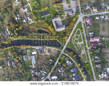 Top view of the village. One can see the roofs of the houses and gardens. Road and water in the village. Village bird's-eye view.