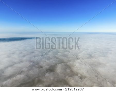 In the skies above the fog. Sunrise over the fog. Clouds near the ground.