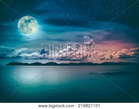 Beautiful landscape view of the sea with many stars . Attractive dark sky and full moon on seascape to night. Serenity nature background. High contrast and vintage effect tone. The moon taken with my own camera.