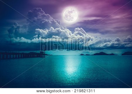 Beautiful landscape view of the sea. Colorful sky with clouds and bright full moon on seascape to night. Serenity nature background outdoor at nighttime. The moon taken with my own camera.