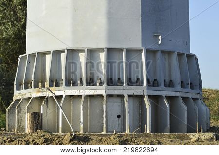 The base of the column power line support. Massive metal pole.