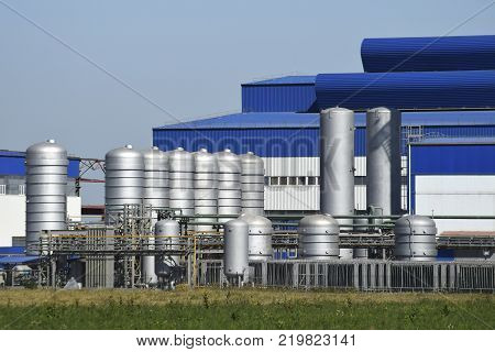 Big plant for processing scrap metal. Huge factory old metal refiner. Blue roof of the factory building. Exhaust pipes, radiators, cooling industrial units as well as office buildings.