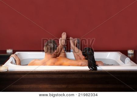 Portrait of loving couple embracing, lying in jacuzzi, relaxing.