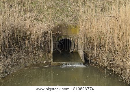 Gateway between the channels of the irrigation system of rice fields. Concrete underground construction.