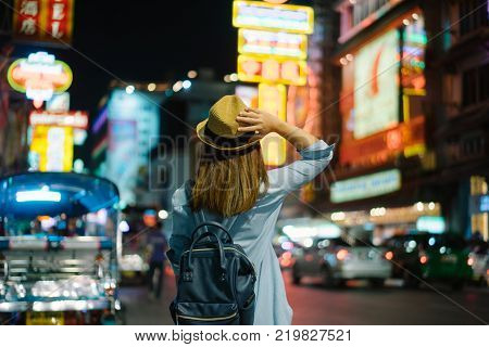 Young Asian Woman Traveler With Blue Backpack And Hipster Hat Looking Night View On Road With Tuk Tu