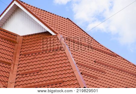 The roof of corrugated sheet red, orange. Roofing of metal profile wavy shape.