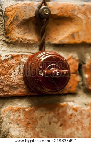 Light switch on a brick wall. Switch old model.