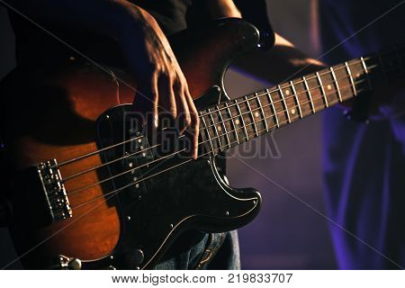 Electric bass guitar player hands soft selective focus live music theme