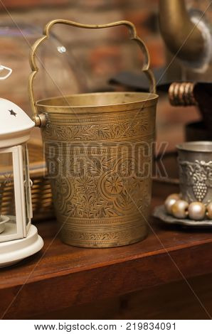 Vintage champagne buckets standing on wooden shelf.