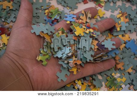 Close up of hand placing the puzzle Hand holding missing jigsaw puzzle piece