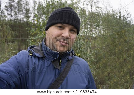 Man sitting and makes selfie in forest. holding hands.
