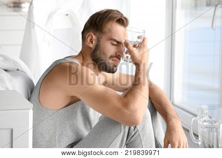 Morning of young man suffering from hangover at home