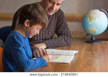 Father and son solving mathematics homework togehter helpful parent