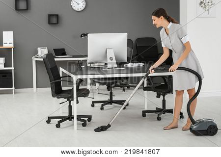 Young woman hoovering floor in office using vacuum cleaner