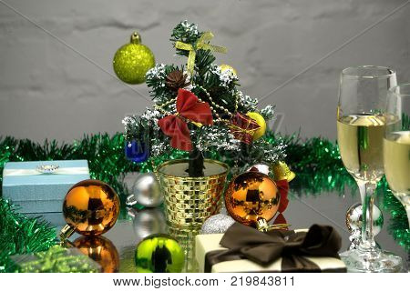 Two champagne glasses red Merry Christmas ball hanging on fir branch under snow and fir-cones over colorful blurred illumination card for new year greeting