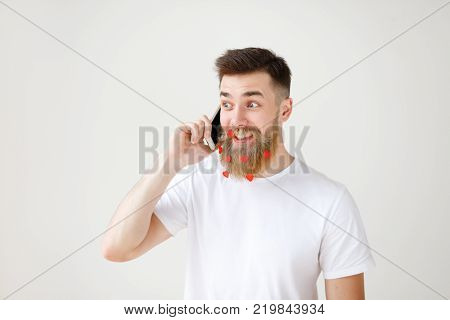 Atrractive smiling bearded male in casual clothes has pleasant talk via smart phone with friend, share news together, has long beard decorated with paper hearts, looks happily aside, isolated on white.