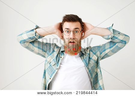 Stupefied surprised man with long beard dressed in fashionable clothes, keeps hand on head, stares through spectacles, being amazed to hear shocking news, isolated over white studio background.