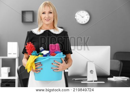 Mature charwoman with cleaning supplies in office