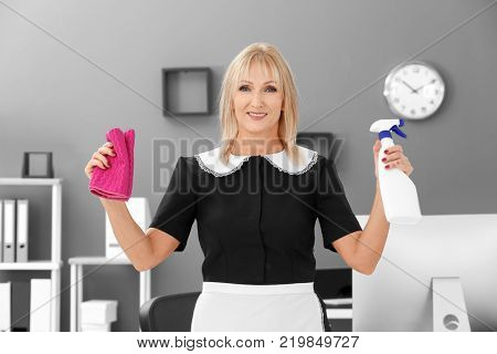 Mature charwoman with bottle of detergent and rag for cleaning office