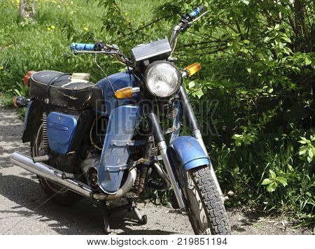 Vintage motorcycle standing in in the rays of sunlight. Side view