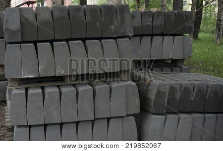 Stack of concrete curbstone. Construction process the dark one