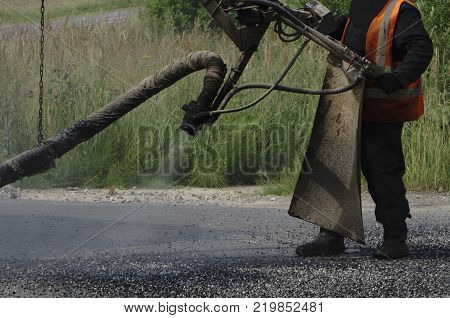 Close view on the worker and the asphalting machines