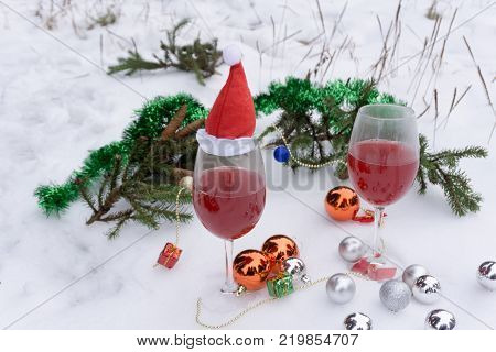 Wine glass with red sparkling wine on a table on a blurred background of christmas lights