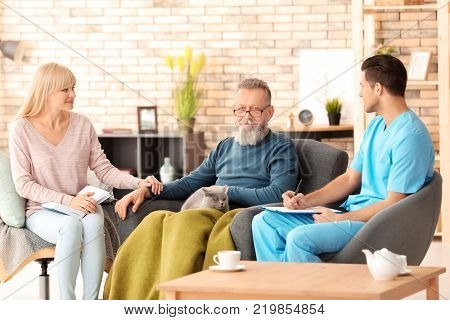 Caregiver with senior man and his daughter at home