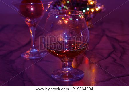 Christmas tree branch glass new year's toy. Glass with drink and a Christmas ball on violet background. Christmas ball and glass. A glass of alcohol and a Christmas ball
