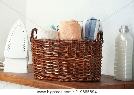 Basket with laundry, iron and detergent on wooden table