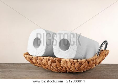 Wicker basket with rolls of paper towels on table against light background
