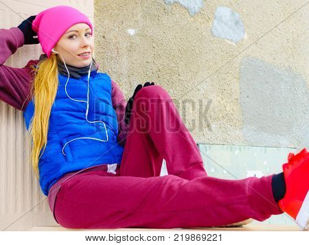 Outdoor sport exercises sporty outfit ideas. Woman wearing warm sportswear relaxing after exercising outside during cold weather.