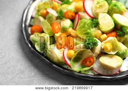 Plate with yummy brussel sprouts salad on table, closeup
